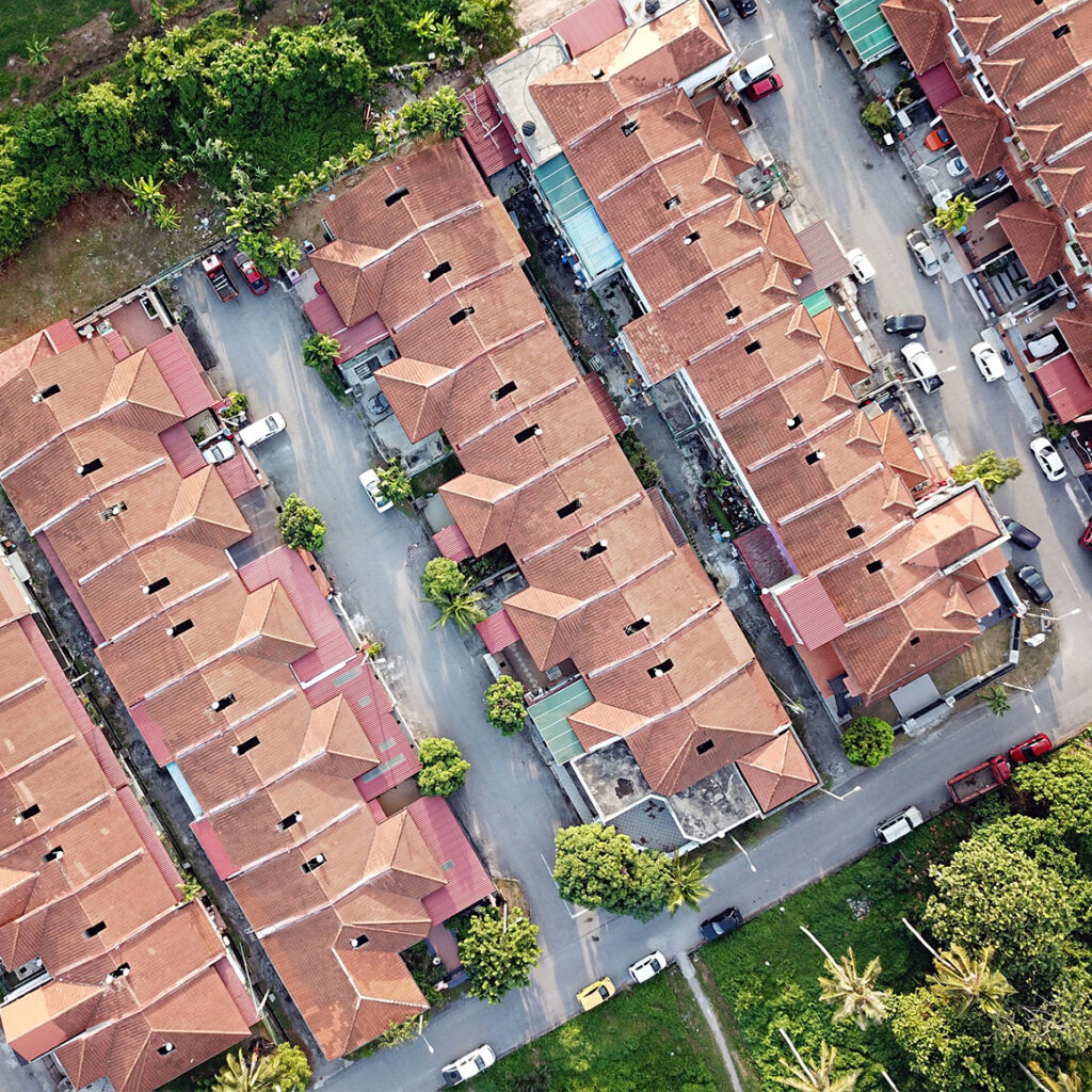 an arial photo of a housing complex with cars parked around the property and trees lining the edges