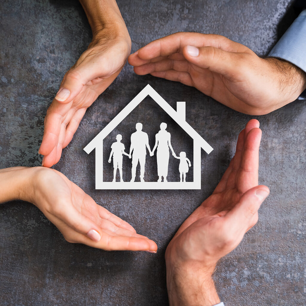 four hands encircling a paper cutout of a house with a family inside of it