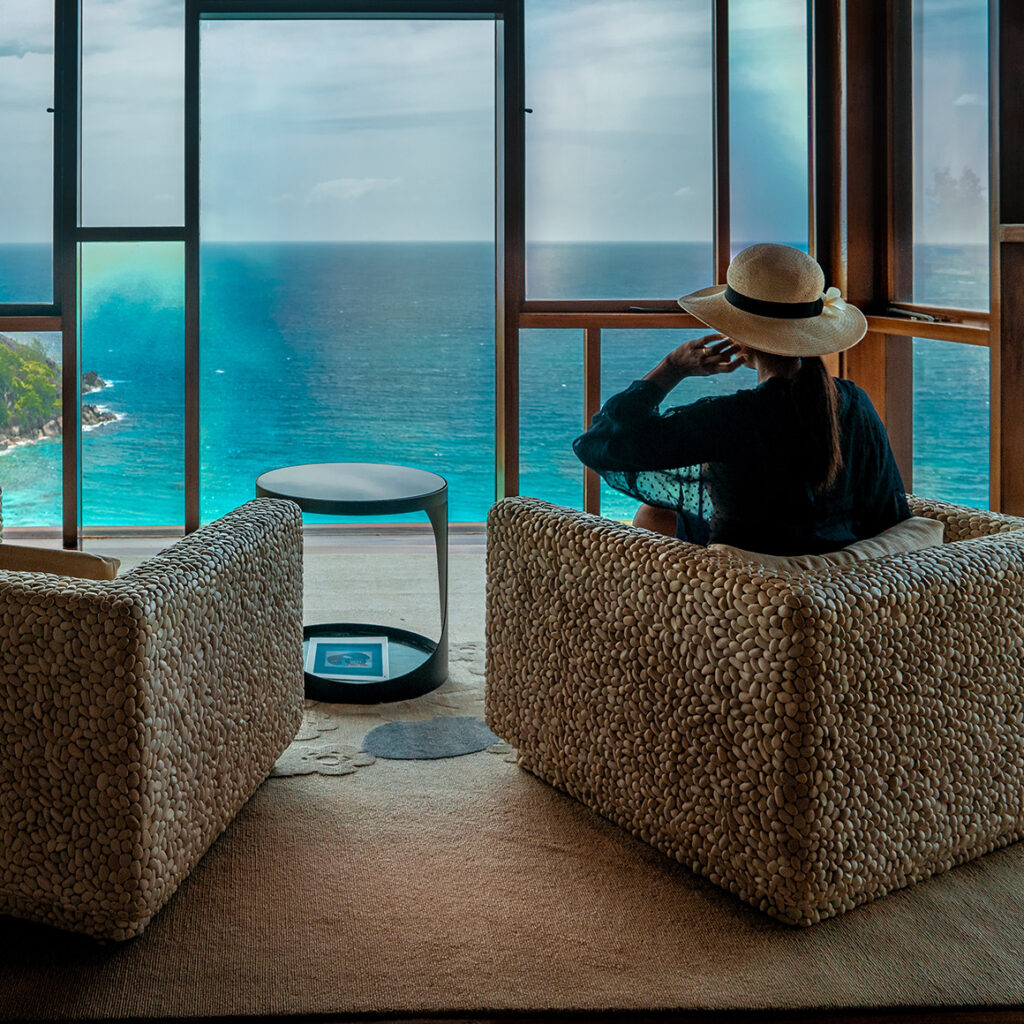 a woman sitting on a chair looking pensively out the window in front of her which overlooks a vast ocean