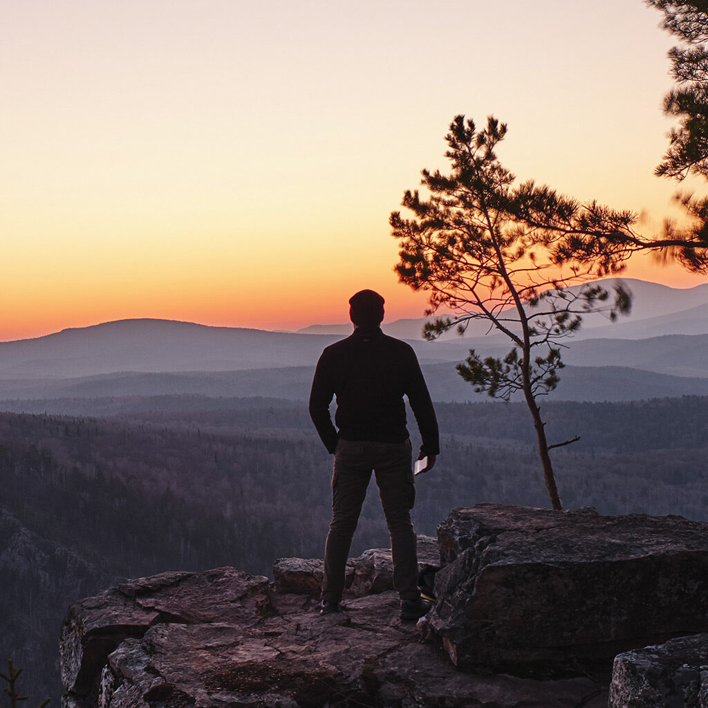 an image of a man at the top of a mountain looking pensively into the distance